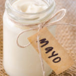 Jar of mayonaise with 'mayo' label on hessian material, a salad dressing or sandwich condiment